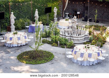 Beautiful wedding set up. Wedding ceremony in the garden with sculptures and fountain