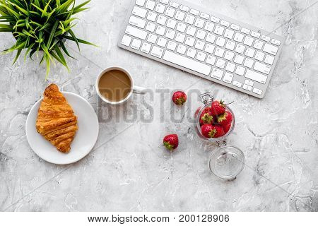Dessert fo light lunch at workplace. Coffee, strawberry, croissant near keyboard on grey background top view.