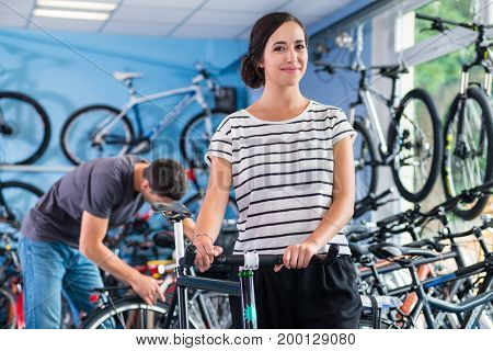 Couple in bike shop buying bicycle after buying