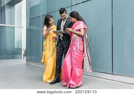 Three Indian business people using high-tech devices outdoors during break at work
