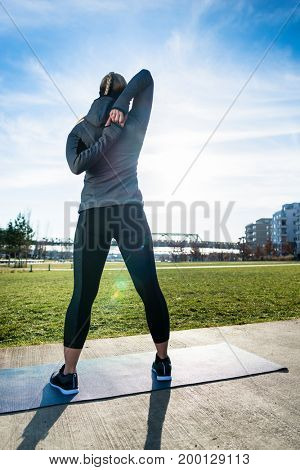 Rear view of a fit woman practicing a shoulder stretch as routine exercise for warming up before outdoor workout in the park