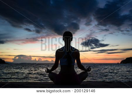 Full length rear view of a fit woman sitting in lotus position while practicing yoga on the beach at twilight during summer vacation in Flores Island, Indonesia