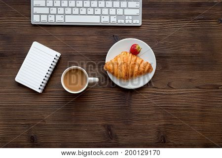 Dessert fo light lunch at workplace. Coffee, strawberry, croissant near keyboard on wooden background top view.
