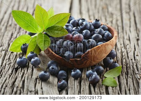Blueberry with leaves on a wooden board