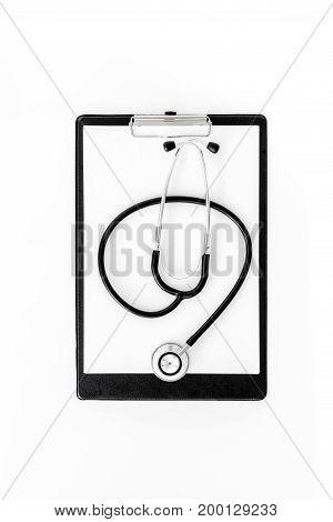 Doctor's table. Clip pad and stethoscope on white background top view.