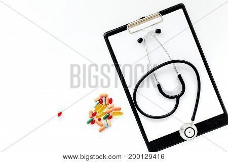 Doctor's table. Clip pad, stethoscope, pills on white background top view.