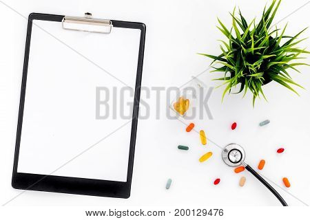 Doctor's workplace in clinic. Accessories. Clip pad and colored pills on white background top view mockup.