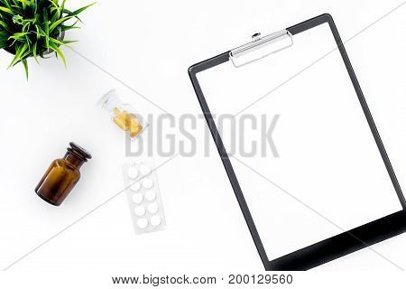 Doctor's workplace in clinic. Accessories. Clip pad, blister and glasses with pills on white background top view mockup.