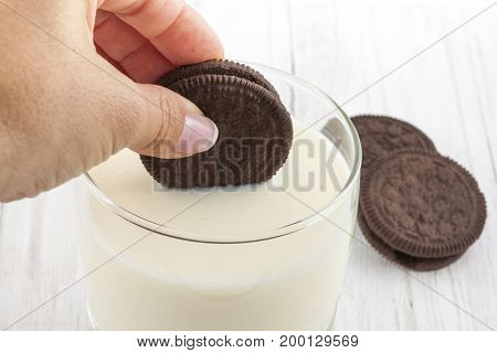 Close up of a woman dunking chocolate cookies in milk