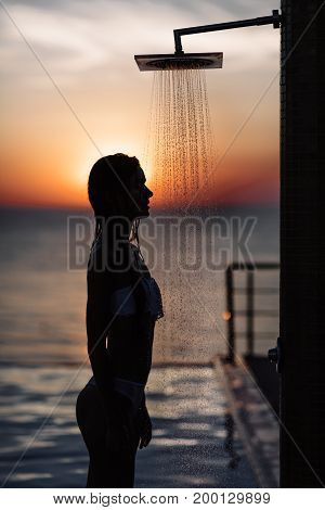 Silhouette Of A Beautiful Girl With A Perfect Figure In The Shower At Sunset In The Sea And Pool