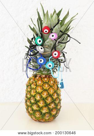 evil eye bracelets advertisement on pineapple - exotic fruit with greek jewelry