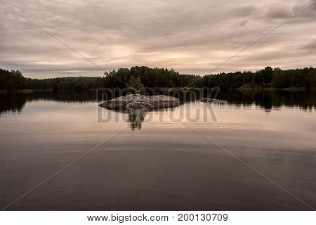 Summer night by lake with overcast sky