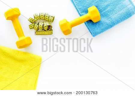 Fitness for losing weight. Dumbbells and measure tape on white background top view.