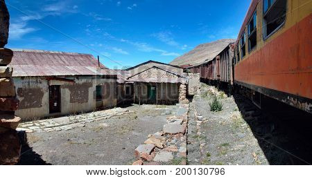The abandoned railway wagons with damaged warehouse buildings, Peru