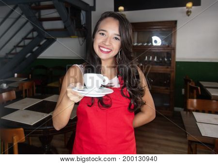 Laughing caucasian waitress with coffee working in a restaurant