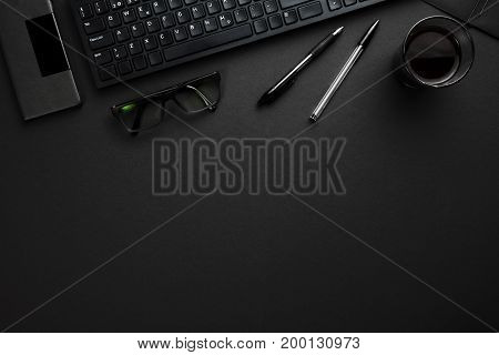 Directly above shot of computer keyboard with pens, eyeglasses and smartphone on gray desk
