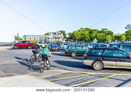 Bar Harbor USA - June 8 2017: Father and son riding bicycles on parking lot of dock with boats on water in downtown village in summer