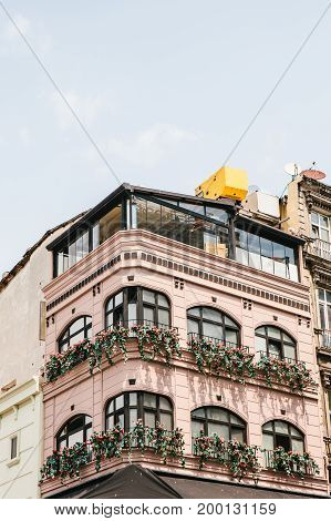 Daytime vew of city building facade with floral balconies.