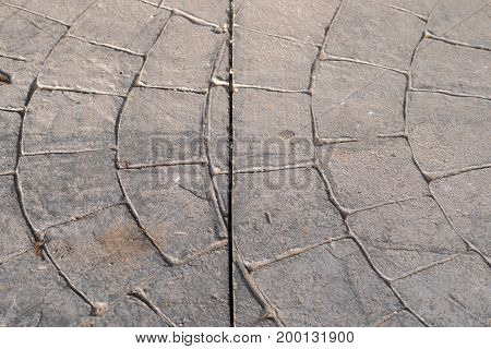 expansion joint without fracture or fissure. Dilatation joint on surfaces of stamped concrete pavement outdoor, appearance colors and textures of paving stone on cement, flooring