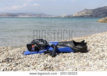The fins, mask and snorkel diving lie on the stone beach near the sea