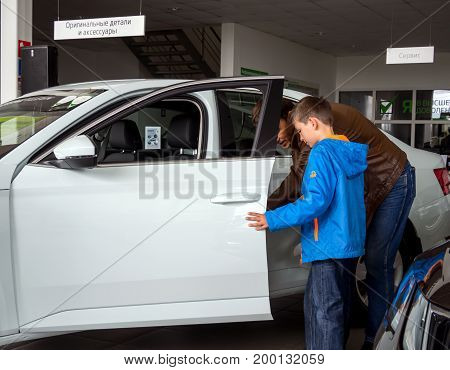 Voronezh, Russia - June 04, 2017: A man with a child is studying the interior of a new car through an open door