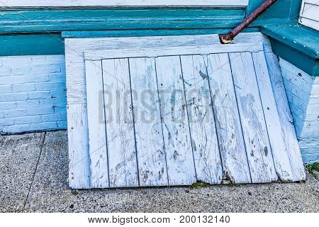 Wooden Blue Antique Door To Basement Entrance Of House In Downtown By Street