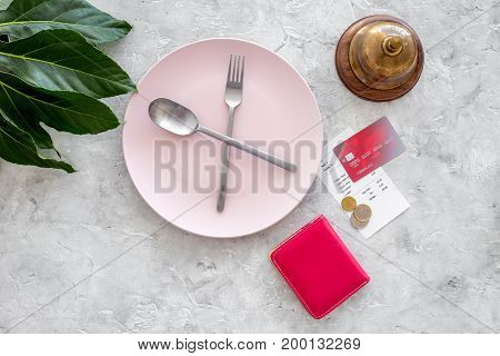 Meal is over. Bill, wallet and bank card near plate with crossed spoon and fork on grey stone table top view.
