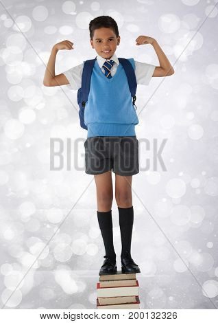 Digital composite of Schoolboy flexing strong arms while standing on books and bokeh bright background