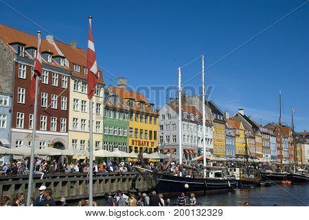 Copenhagen, Denmark - June 2013: Colorful houses of Copenhagen's landmark Nyhavn, with lots of people along the waterfront, in June 2013