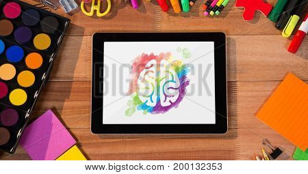 Digital composite of Tablet on a school table with colored brain on screen