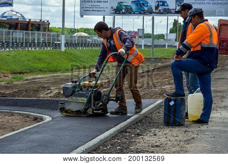 Voronezh, Russia - June 04, 2017: Formation of an asphalt layer on the sidewalk using a vibrating machine