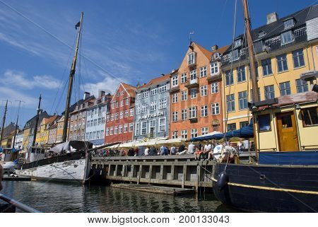 Copenhagen, Denmark - June 2013: Colorful houses of Nyhavn, Copenhagen's landmark and tourist attraction, with lots of people strolling along the waterfront in June 2013