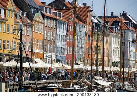 Copenhagen, Denmark - June 2013: Colorful houses of Copenhagen's landamrk Nyhavn, with lots of tourists along the waterfront in June 2013