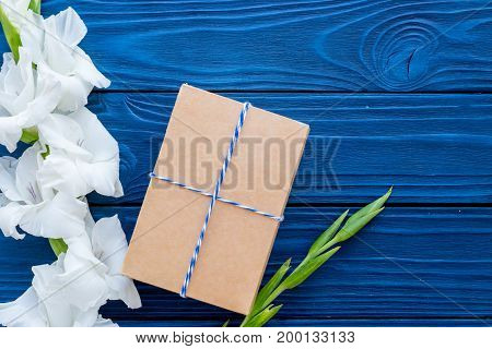 Preparing to celebration. Box in kraft paper near flower gladiolus on blue wooden table top view.