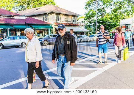 Bar Harbor USA - June 8 2017: Happy people crossing sidewalk street in downtown village in summer on main road
