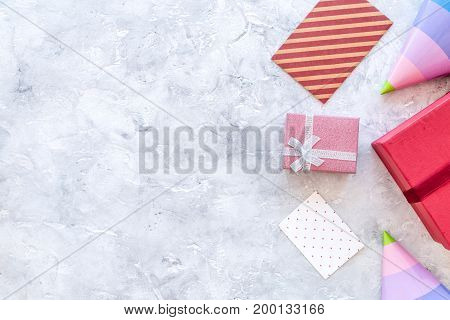 Preparing to celebration. Colored gift boxes and party hats on grey stone background top view.