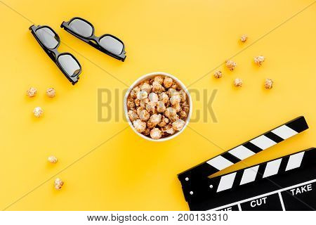 Ready to watch film. Clapperboard, glasses and popcorn on yellow background top view.