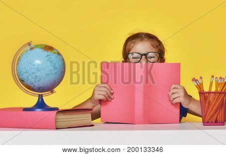 Back to school and happy time! Cute industrious child is sitting at a desk indoors. Kid is learning in class on background of bright yellow wall. Girl reading the book.