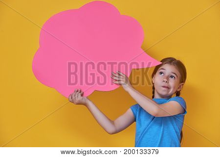 Cute little child girl with cartoon thought on colorful background. Yellow, pink and blue colors.