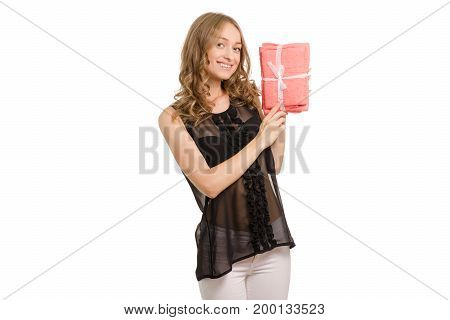 Beautiful young girl in the hands of bed linen and towel on white background isolation gift