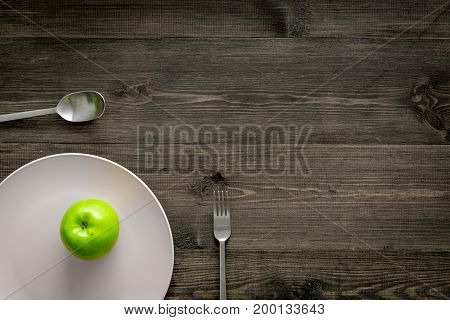 Slimming diet. Apple at plate on wooden background top view.
