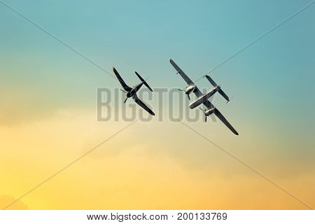 Silhouette of an airplane performing flight at airshow. F4U and B25 planes.
