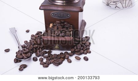 Closeup of coffee grinder full of roasted beans on the white