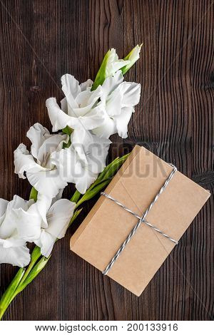 To wrap a gift. Box in kraft paper near flower gladiolus on dark wooden table top view.