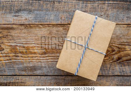 To wrap a gift. Box in kraft paper on rustic wooden background top view.