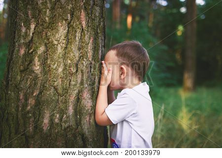 Little Caucasian boy closing his face with hands as if playing hide and seek or scared of something. Hiding face. Closed face.