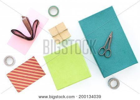 To wrap gift. Box, paper, envelope, thin cord, card, ribbon sciccors on white background top view
