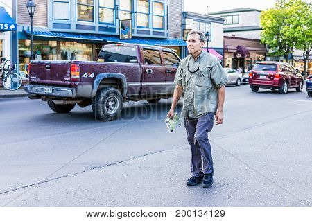 Bar Harbor USA - June 8 2017: Lost tourist man holding map crossing sidewalk street in downtown village in summer on main road