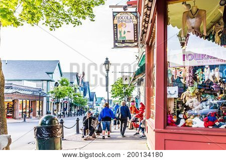 Bar Harbor USA - June 8 2017: People walking and sitting in Maine downtown village in summer evening by chocolate emporium