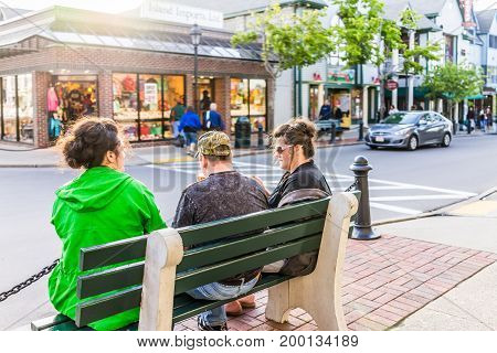 Bar Harbor USA - June 8 2017: People on benches in Maine downtown village in summer evening eating ice cream